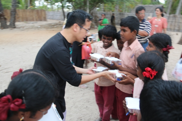Henky giving out a meal to the HoPE Center children